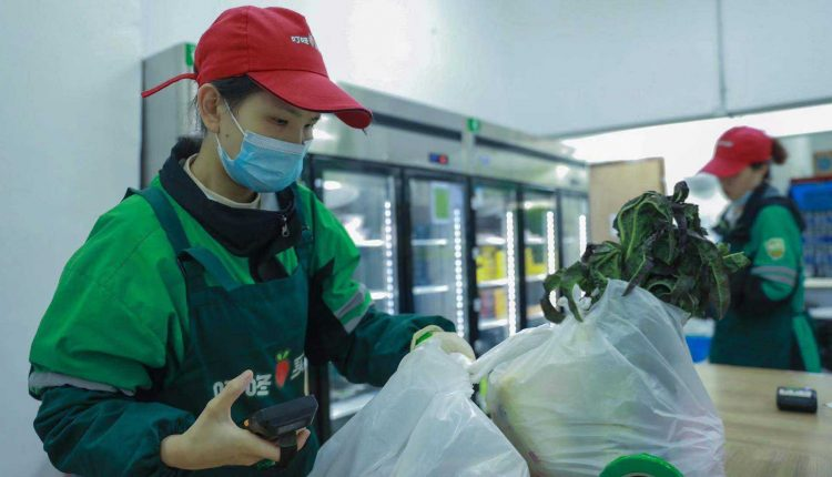 Chinese grocery delivery company clings to gains after slashing IPO